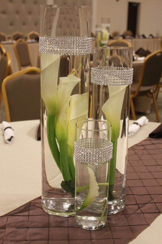 White calla lilies curled into circular glass vases make a