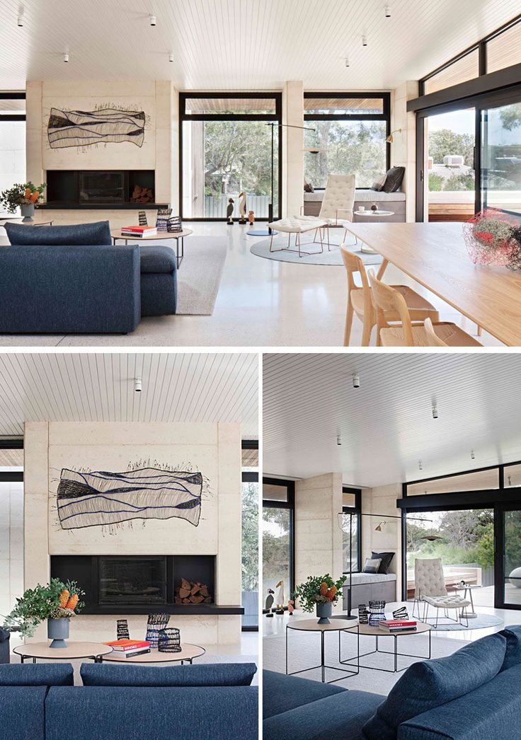 This modern living room is focused on a fireplace, while the dark blue couch is adds a touch of color to the interior. Black framed aluminium doors and windows fill the open room with plenty of natural light.