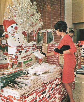 All decked out in red dress and pearls (and black gloves. Wow.), a young woman looks over some snowballs for sale at the Hughes Market in Westdale (L.A. area) California