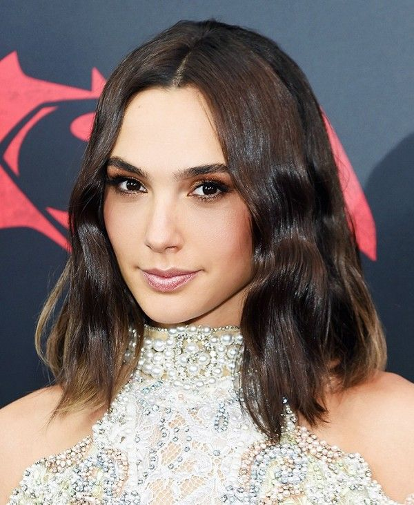 Gal Gadot goes for a sultry beauty look with a wavy lob, a shimmery smoky eye, and a nude pink lip color