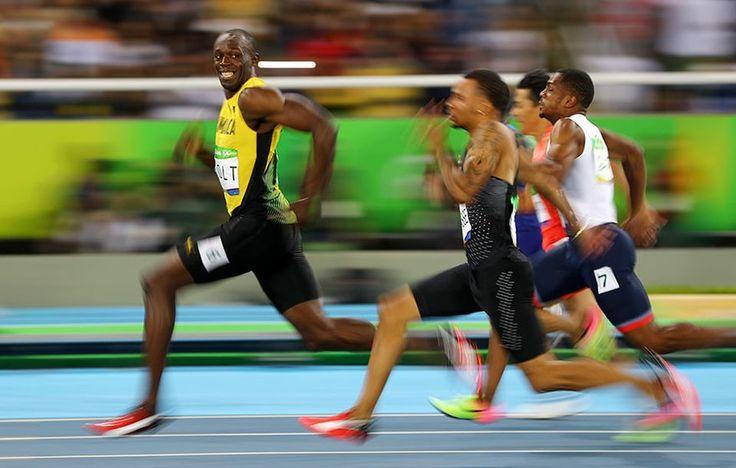 Usain Bolt z Jamajki zerka na Andre De Grasse z Kanady, w trakcie półfinału biegu na 100 m mężczyzn, na Igrzyskach Olimpijskich w Rio