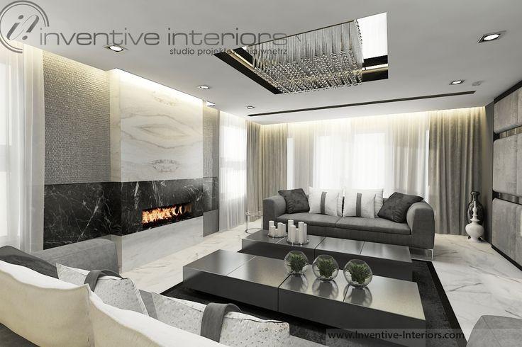 Projekt salonu Inventive Interiors - ciemne szare sofy w luksusowej aranżacji salonu z pięknym podłużnym kominkiem