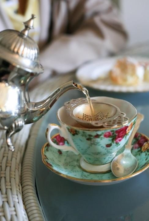 Vintage tea cup and saucer with traditional tea pot, metal tea strainer