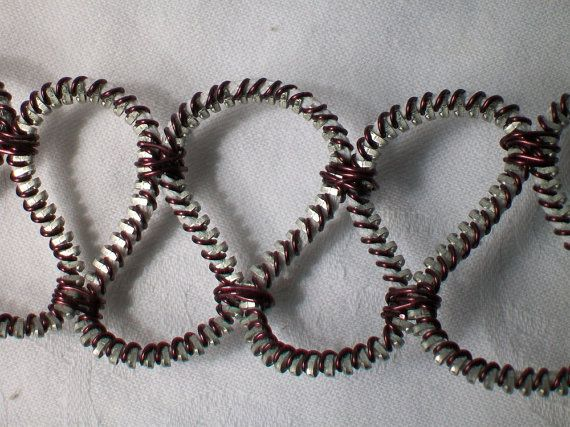 Dit is een armband gemaakt van de ene kant van een lange rits. Een paarse (koperdraad) was gewikkeld tussen elke tand op de rits. De draad vandaan kwam binnen een oude TV-toestel. Vervolgens was de rits samen geplakt op bepaalde plaatsen om de lus-ontwerp te maken. Kleurkeuze is voor