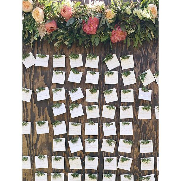 For the escort-card display at one wedding in Ojai, California, each hand-lettered card was threaded with a sprig of fresh rosemary.