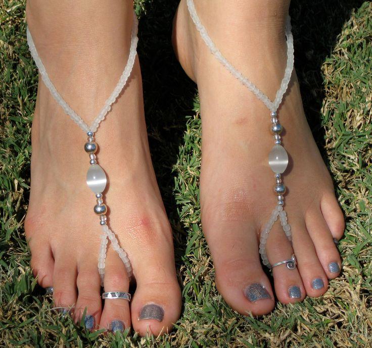 Un paio di sandali a piedi nudi bianchi e argento. Composto da perle di vetro e cavo estensibile gioielli. Ogni pezzo è unico e fatto a mano. Si può indossare questi per qualsiasi attività a piedi nudi come il sole, danza del ventre, yoga, Pilates o oziare in spiaggia. Possono essere indossati anche in acqua per il divertimento a bordo piscina o nelloceano. Indossare con infradito semplice per aggiungere interesse al tuo look. Può anche essere indossati attorno al dito/polso come bracciali…