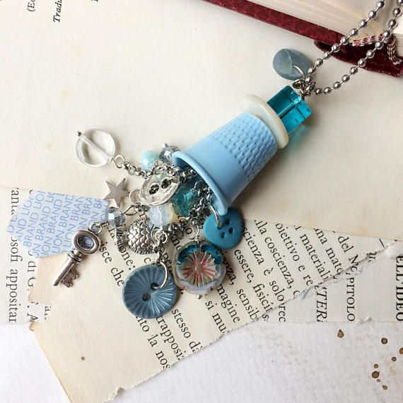 Long necklace with blue thimble pendant and charms. Re-Fashion
