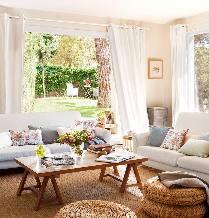 Abierta al exterior.Pufs de fibra vegetal de Ikea. Sobre la mesa de centro, de Cottage Little House, cesta de hierro y vasos de Velafusta.