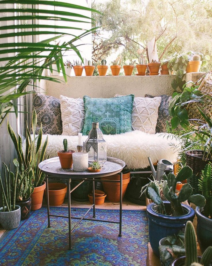 Balkon im Boho Look mit Tabletttisch, Kakteen und tropischen Pflanzen