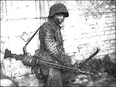A young machine-gunner totes an MG-42 at Caen in northern France shortly after D-Day.