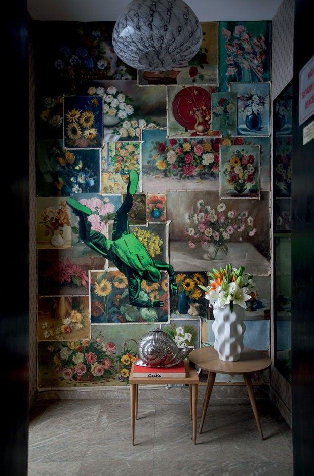 No hall do elevador, naturezas-mortas formam uma colagem sobre a parede, junto ao vaso branco da Holaria e lustre antigo de Murano
