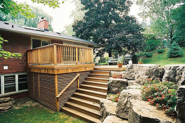 This clear cedar deck was built by Hickory Dickory Decks in the the 1990's in Ancaster Ontario. The stairs cut into the stone wall.