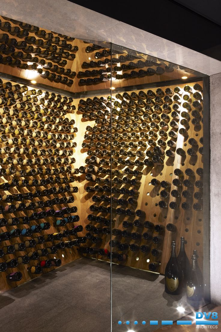 Ellerman House Wine Gallery Champagne Cellar. Traditional riddling racks given a new modern twist in oak.  Mirror extenzo stretch ceiling to reflect and create movement and depth.