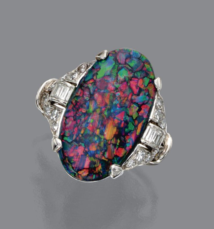 BLACK OPAL AND DIAMOND RING, CIRCA 1920.  The oval-shaped black opal measuring approximately 20.5 by 11.2 by 4.9 mm., the sides accented with buckle motifs set with single-cut and baguette diamonds, mounted in platinum, size 7¾.