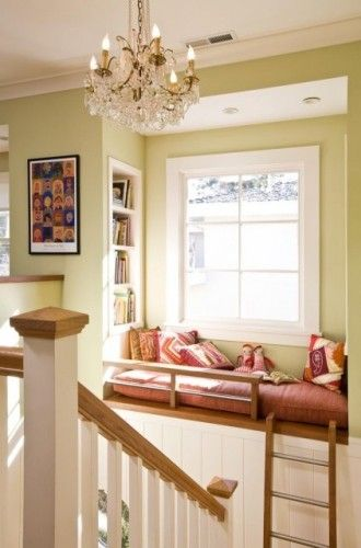 raised window landing on stairs turned into reading nook with a ladder