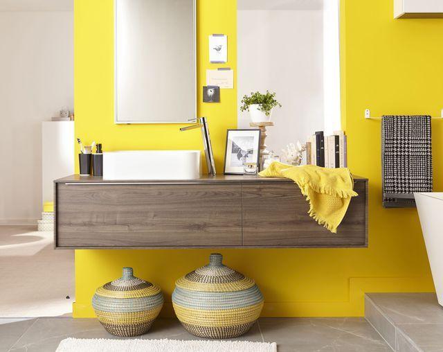 Salle de bains jaune flashy et touche de déco en bois, vases en céramique posés au sol