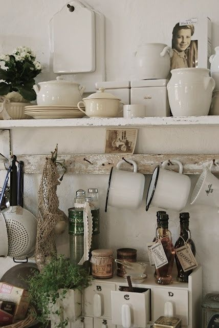 Country kitchen display made w/an old board and a wooden strip w/used, rusty nails.