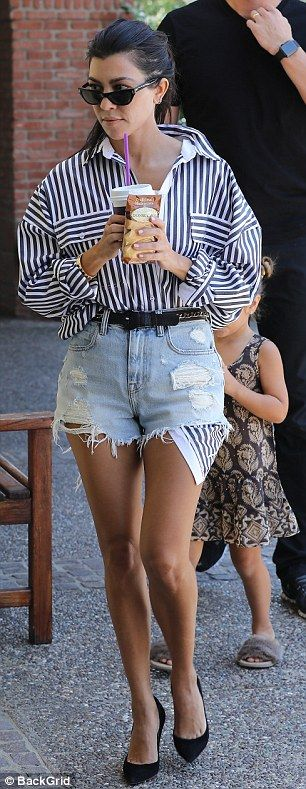 Signature style:The former girlfriend of Scott Disick tucked a baggy black and white striped dress shirt into the pair of tiny shorts