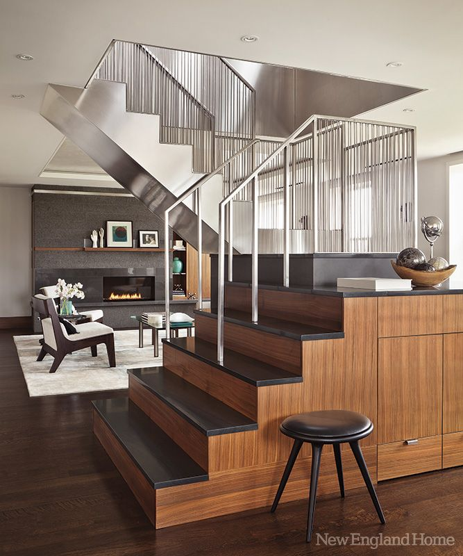 a sculptural staircase of stainless steel walnut and concordia stone separates a long low