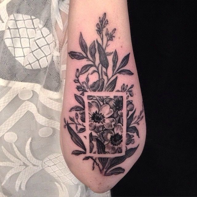 I love the use of negative space on this black and white floral forearm tattoo!