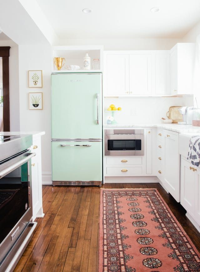 White cabinets with light aqua blue fridge and wooden floors