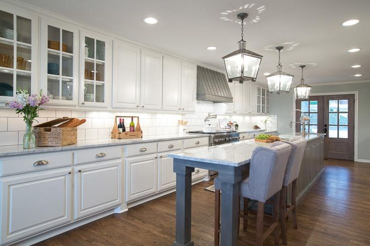 After the makeover, it's hard to believe this is even the same kitchen! A wall was removed to allow for a beautiful long kitchen island and to create an open, airy feel throughout the space. Bright white cabinets look stunning against the warm hardwood floors, while pendant lights and stainless hardware bring an updated feel to the charming kitchen.