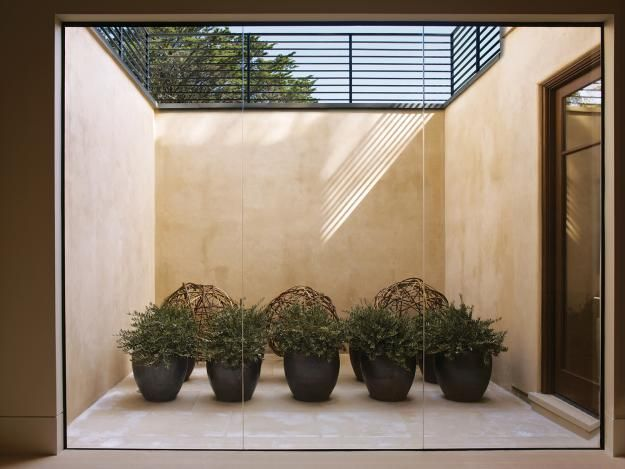 Pebble Beach, California, house, an east- and south-facing patio allows natural light into an indoor basement entertaining area. Planters and sculptural balls made of willow enliven the space
