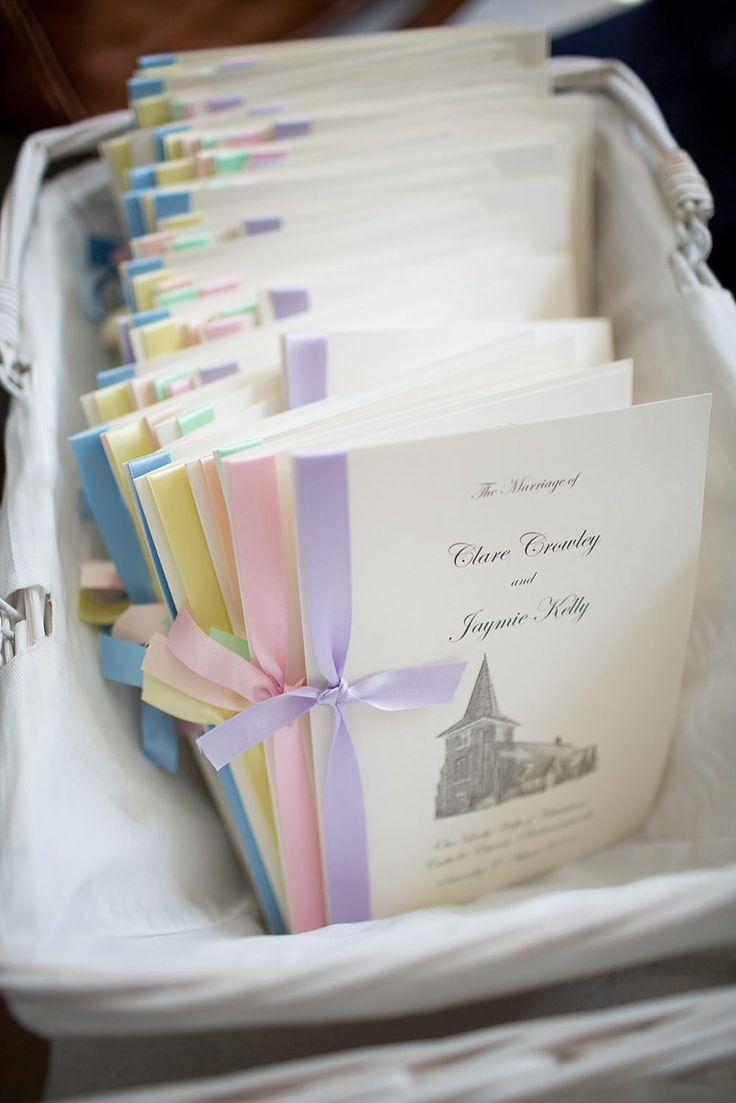 wedding programmes with different coloured pastel ribbons -  Image by Fiona Kelly - Pastel Wedding With Ribbon Details At Hunton Park With Bride In Original Always & Forever Designed Gown And Bridesmaids In Pastel Gowns From Kelsey Rose With Groom And Groomsmen In Suits From Hugh Harris