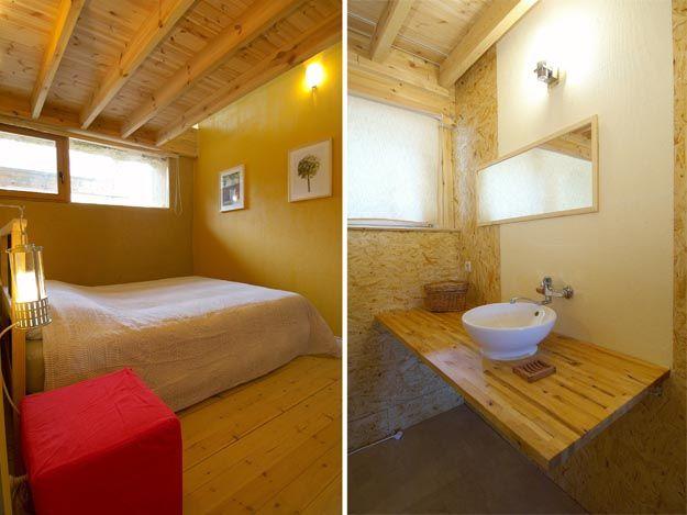 Slaapkamer met lemen wanden, lichte houten planken vloer en dito plafond tussen de balken doorl