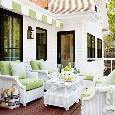 Nostalgic white wicker furniture and a striped cabana awning create a striking contrast to the modern black windows on this second-floor porch.