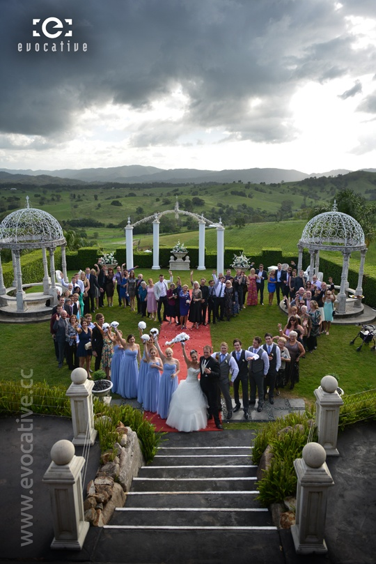 Group shot of the entire wedding party and guests in a giant heart shape, with beautiful countryside and mountains in the background at Glengariff Historic Estate and Winery. #WeddingPhotography