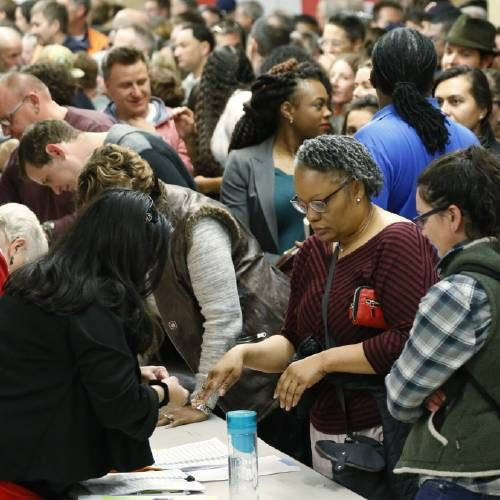 photo - Voters crowd in to check with precinct captains at a Democratic caucus late Tuesday, March 1, 2016, in Denver. Colorado is one of 12 states casting votes for party nominees on Super Tuesday, which offers candidates the chance to garner the biggest single-day delegate haul of the nomination contests. (AP Photo/David Zalubowski)