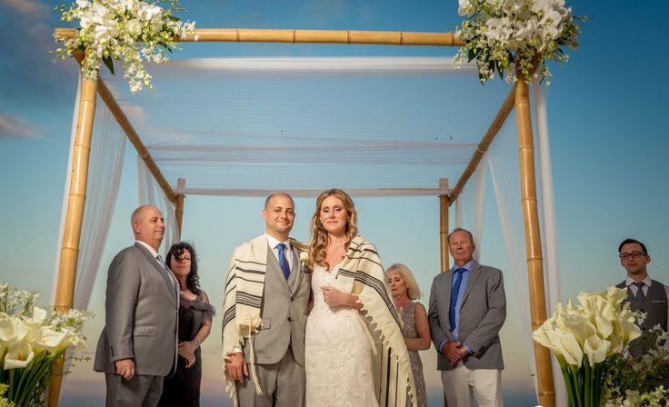 Bride and groom pose under the chuppah after their beach wedding ceremony #destinationwedding
