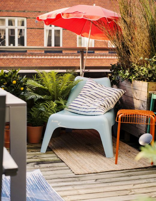 A blue lounge chair in the corner of the balcony surrounded with lots of plants and a big umbrella.