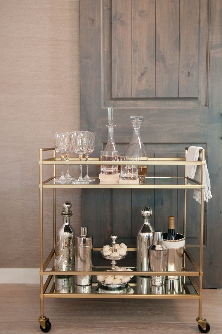 A chic bar cart, like this one full of glam mixed metallics, is a must have for a young couple like Lauren and Jason who frequently entertain.