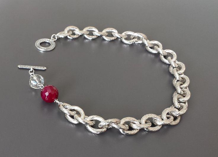 Collana in maglia di metallo argentato arricchita di cristallo e grande agata cherry. Importante chiusura a cerchio e barretta anticata.