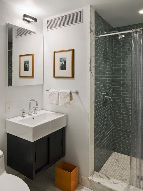 Banheiro com azulejos retangulares cinza na parede do box, e retangulares brancos no chão. Box de plastico transparente, soleira de mármore dividindo o banho do banheiro. Paredes pintadas no restante do banheiro, um pequeno quadro com molduras de madeira enfeita o canto da pia. 15 Inspirações para decoração do Banheiro