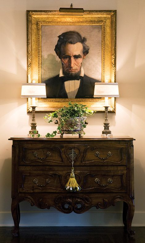 The warmth of the two candlestick lamps is enough to soften even the austere visage in the painting. The beautiful gilded frame adds richness to Lincoln's portrait. A tasseled key hanging from an antique chest accents the verticality of this arrangement.