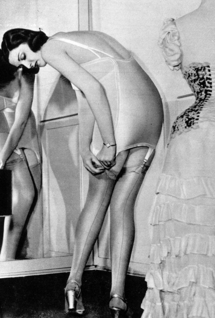 While fastening her stockings, her outfit waits patiently on its dress form. - MarieClaire.com