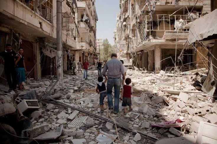 Un padre camina con sus hijos por una calle destruida de Aleppo, Siria