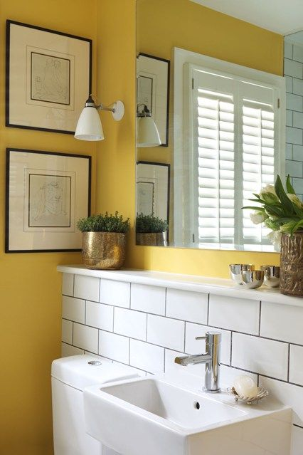 Bright yellow paint works as a perfect foil to white industrial tiles and gold accessories in this London bathroom.