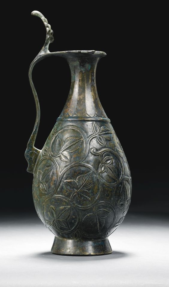 Umayyad or Abbasid bronze ewer with carved decoration, Persia, circa 8th century A.D.  The pear-shaped body with thin ribbed neck and flattened rim designed as two birds, the curved handle with dragon-head terminal and rising palmette thumbpiece, chiselled with foliate scrolls around a central split-palmette issuing a lotus bud with engraved details, 27 cm high. Private collection
