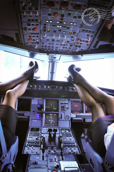 Two stewardesses relax and put their feet up in the cockpit.