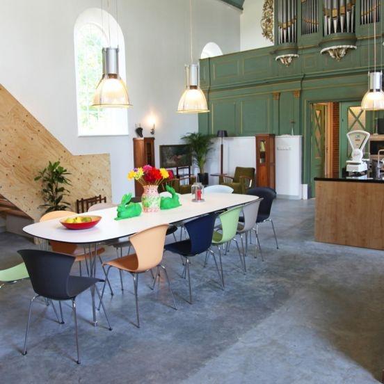 De eettafel: In de kerkzaal staat een lange moderne leeftafel voor 10 personen.