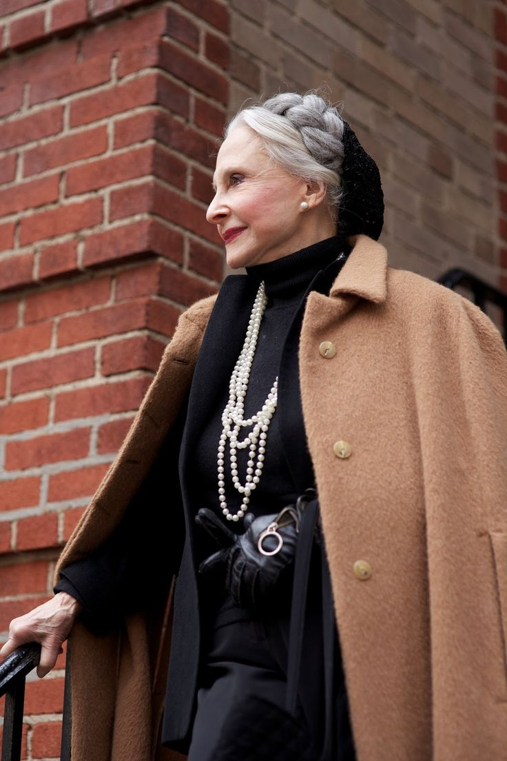 stylish at any age -- ADVANCED STYLE.  crown braid. black slouchy hat/snood. cascading pearls. fitted black sweater. black leather gloves. pearl post earrings. camel car coat. black jacket. black fitted high waisted trousers or cigarette pants. chanel perfume.