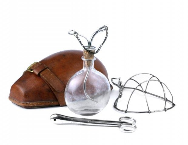 Esmarch's chloroform dripping bottle in a shaped leather case, used for administering anaesthetic in the field in the late 19th century.    The clear glass bottle which would have held the ether or chloroform has a flat and convex surface so as to fit the case. The sealing cork contains two metal tubes which can be closed with a pin and stopper.  The face mask would have been covered with gauze onto which the anaesthetic would be dripped. There is also a pair of tongue holding forceps.