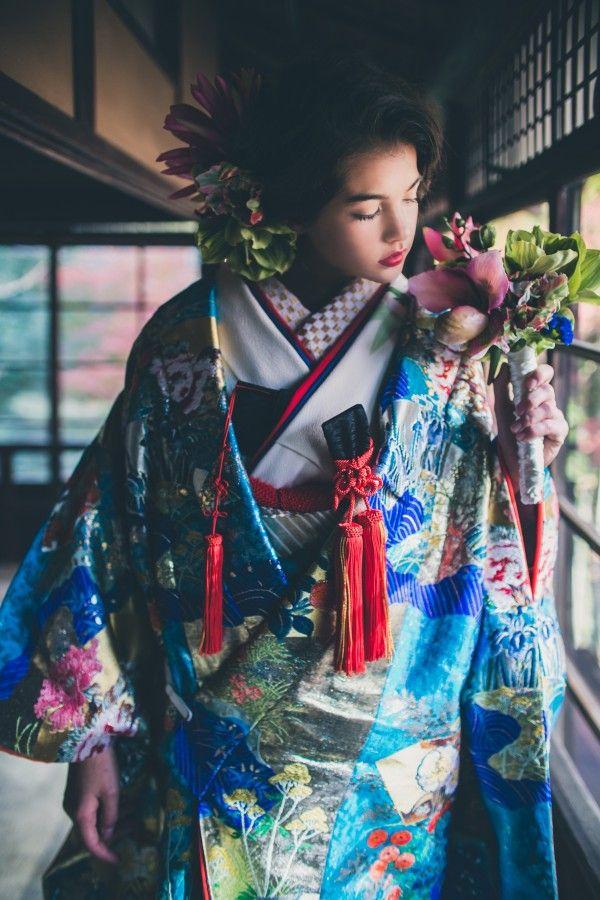 『青道長取秋草』鮮やかな青色の流水が大胆に表現されながら、ところどころに散りばめられた橙や桃色の花々、朱赤のふきが全体を引き締めます。金糸と銀糸をふんだんに使った、色鮮やかで他には類を見ない輝きを放つ一着です。– 南青山の花嫁着物レンタルサロン CUCURU(くくる)