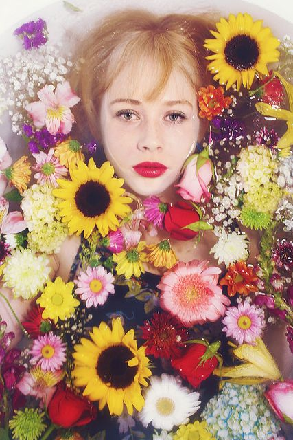 it looks like she is in a flower bath,it looks very good though as she has a fully focused face looking directly at the camera.