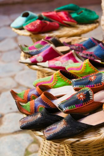Moroccan slippers for sale displayed on woven stools - I wanted (still do) every color when I shopped for my babooches!