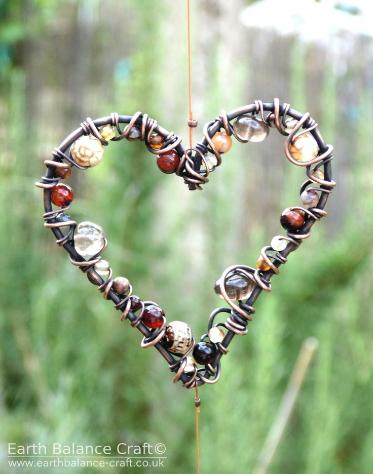 This sun catcher has three heart shaped hanging ornaments made from copper wire wrapped with agate and quartz beads.